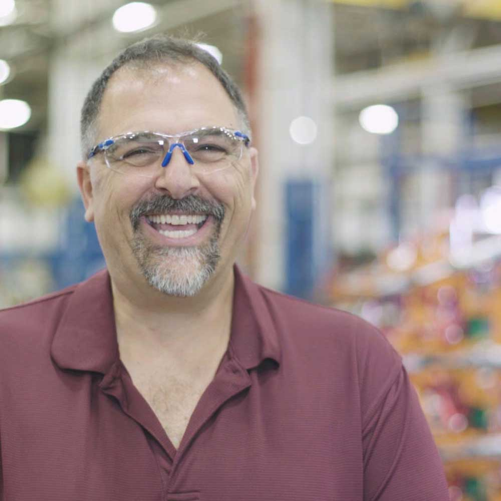 Valiant TMS team member wearing safety glasses and smiling in manufacturing plant