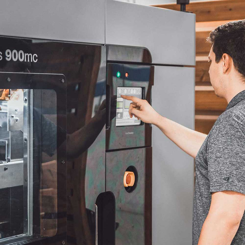 Valiant TMS team member operating 3D printing machine