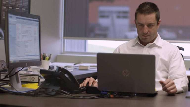 Valiant TMS sales account manager working on laptop.